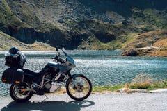 Affärsföretagmotorcykel i höstbergen av Rumänien Moto turism och motohandelsresandelivsstil, medan resa Europa Sjö royaltyfri bild