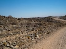 Affärsföretagresaplats på grusvägtur till och med det varma torkade landskapet för Namib öken som vaggar berghorisonten med den l Arkivfoton