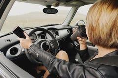 Affärsflicka i ett läderomslag som kör en bil som talar på telefonen arkivbild