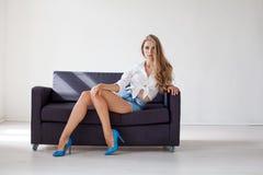 Affärsflickablondinen sitter på en svart soffa i kontoret royaltyfri fotografi