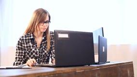 Affärsflickan sitter på en dator i kontorspappersmapparna lager videofilmer