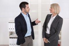Affärsfolk i dräkt och klänning som tillsammans talar: litet samtal Arkivfoton