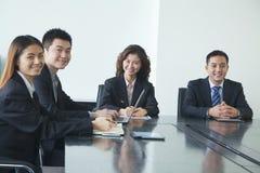 Affärsfolk i mötesrum, le som ser kameran Royaltyfri Foto