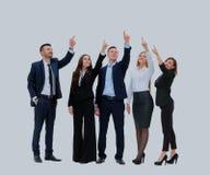 Affärsfolk i rad som upp till pekar och ser kopieringsutrymme som isoleras på vit bakgrund arkivbild