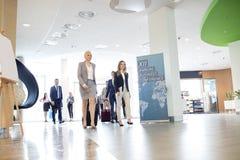 Affärsfolk med bagage som går i konventcentrum royaltyfria bilder