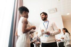 Affärsfolk med konferensemblem och kaffe arkivfoton