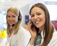 Affärsfolk med telefonen och hörlurar som ger service Fotografering för Bildbyråer