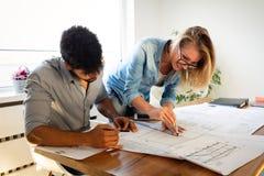 Affärsfolk och arkitekter som tillsammans arbetar på projekt arkivfoto