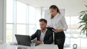 Affärsfolk på bakgrundsflipchart i det vita kontoret, framstickande på tabellen, direktör och anställd, assistentuppehälle i händ stock video