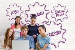 Affärsfolk på ett skrivbord som ser en dator mot den vita väggen med purpurfärgade diagram Arkivfoton