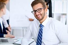 Affärsfolk på möte i regeringsställning Fokusera på gladlynta le bärande exponeringsglas för den skäggiga mannen Konferens som är arkivfoton