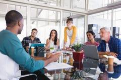 Affärsfolk på skrivbordet under möte arkivfoto