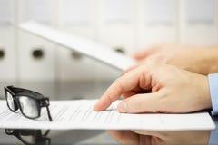 Affärsfolk som analyserar det lagliga eller finansiella dokumentet Arkivbild