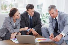 Affärsfolk som analyserar finansiella grafer av deras företag royaltyfri bild