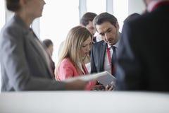 Affärsfolk som använder den digitala minnestavlan i konventcentrum Arkivfoton
