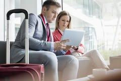 Affärsfolk som använder den digitala minnestavlan, medan sitta på lobbyen i konventcentrum Fotografering för Bildbyråer