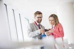 Affärsfolk som använder den smarta telefonen i konventcentrum royaltyfri bild
