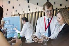 Affärsfolk som använder den smarta telefonen under kaffeavbrott på konventcentret Royaltyfria Foton