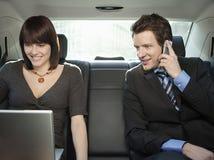Affärsfolk som använder mobiltelefonen och bärbara datorn i bil Fotografering för Bildbyråer