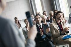 Affärsfolk som applåderar för offentlig högtalare under seminarium Royaltyfria Bilder