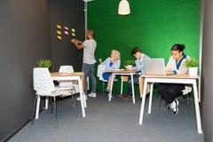 Affärsfolk som arbetar i modern kontorslobby Arkivbild