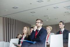 Affärsfolk som deltar i seminarium i konventcentrum Royaltyfri Fotografi