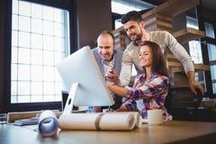 Affärsfolk som diskuterar över datoren i idérikt kontor royaltyfria bilder