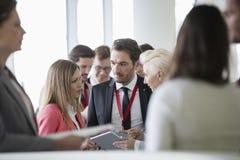 Affärsfolk som diskuterar över den digitala minnestavlan i konventcentrum arkivbild