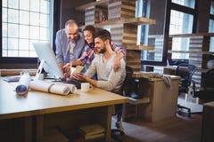 Affärsfolk som diskuterar över dokument på datorskrivbordet arkivbild