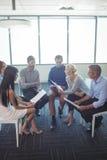 Affärsfolk som diskuterar över dokument på kontoret arkivfoto