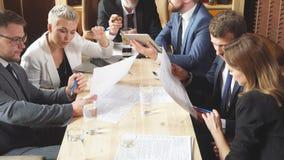 Affärsfolk som diskuterar frågor tillsammans i ett litet konferensrum under möten på ett lysande kontor stock video