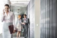 Affärsfolk som diskuterar i korridor med kollegan som använder mobiltelefonen i förgrund arkivfoto
