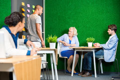 Affärsfolk som diskuterar i modern kontorslobby Arkivfoton