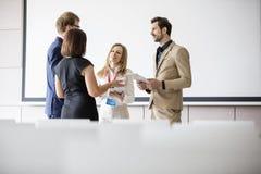 Affärsfolk som diskuterar i seminariumkorridor Royaltyfri Foto