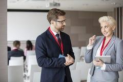 Affärsfolk som diskuterar i seminariumkorridor Royaltyfria Bilder