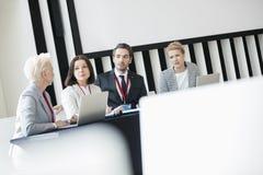 Affärsfolk som diskuterar, medan sitta på skrivbordet i seminariumkorridor royaltyfri fotografi