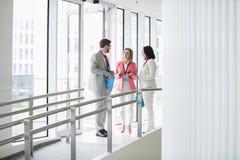 Affärsfolk som diskuterar vid fönsterkonventcentret Arkivbild