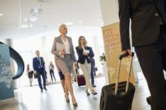 Affärsfolk som drar bagage, medan gå i konventcentrum Arkivfoto
