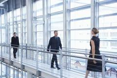 Affärsfolk som går vid räcket i modernt kontor royaltyfri fotografi