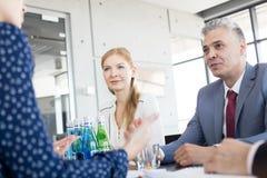 Affärsfolk som har diskussion i bräderum på kontoret Arkivfoton
