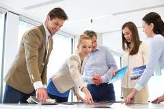Affärsfolk som har diskussion på tabellen i nytt kontor Arkivfoto