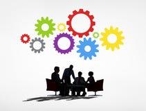 Affärsfolk som har ett möte och kugghjul över Arkivfoto