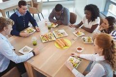 Affärsfolk som har frukosten på kontorskafeterian Royaltyfri Foto