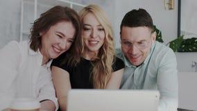 Affärsfolk som har gyckel med en minnestavla i kontoret Stilfulla spektakulära män i exponeringsglas, lycklig brunettkvinna oc stock video