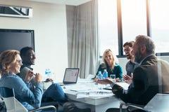Affärsfolk som har tillfällig diskussion under möte royaltyfri bild