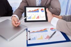Affärsfolk som i regeringsställning diskuterar grafen på den digitala minnestavlan Royaltyfri Bild