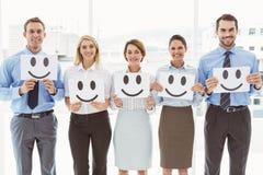 Affärsfolk som i regeringsställning rymmer lyckliga smileys Royaltyfri Bild