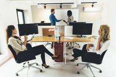 Affärsfolk som i regeringsställning sitter och lär nya tekniker Royaltyfri Bild