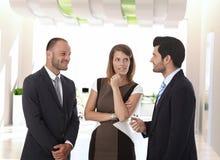 Affärsfolk som i regeringsställning talar korridoren arkivbild