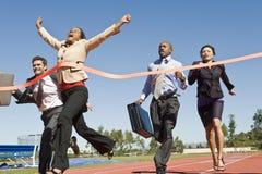 Affärsfolk som korsar den vinnande linjen Royaltyfria Bilder